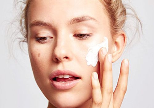 woman with honey blonde hair applying cream to her face