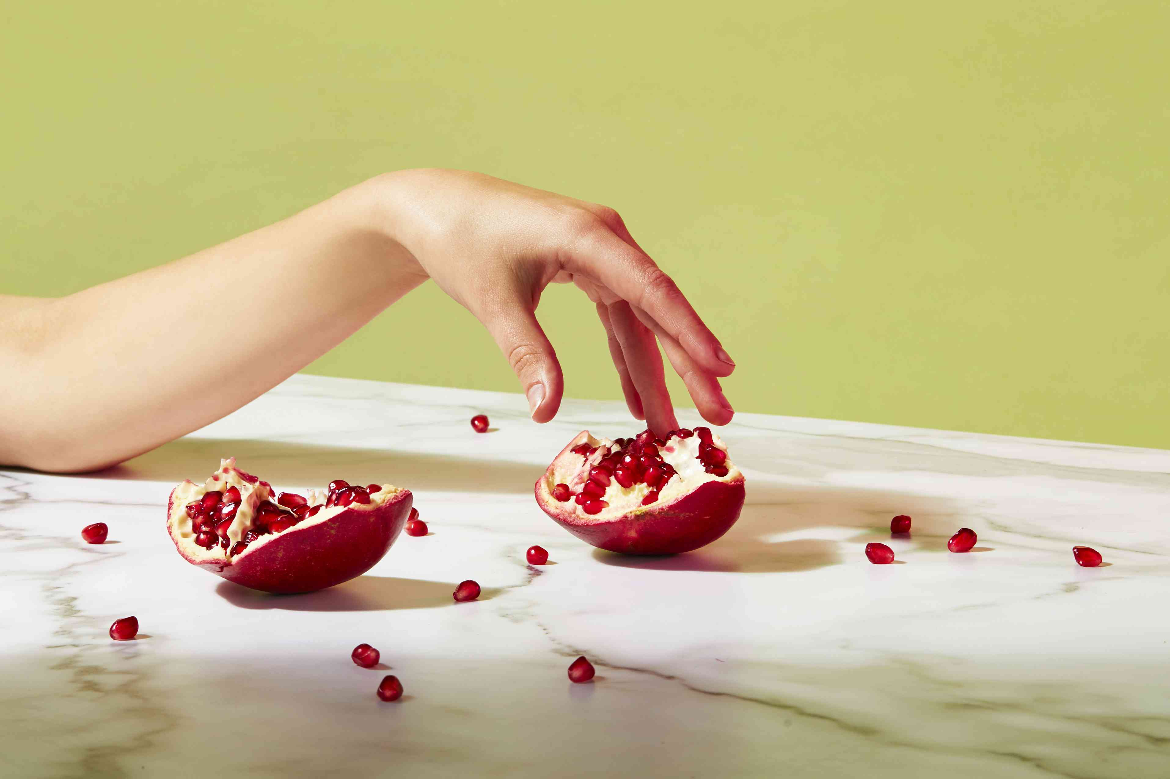 arm and pomegranate in strong lighting