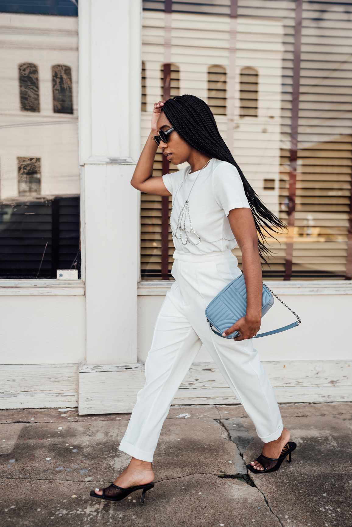 young black woman walking stylish purse blue white
