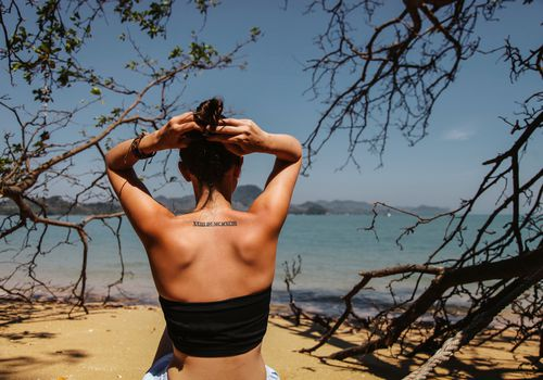 Rear View Of Woman Tying Her Hair At Beach Against Sky