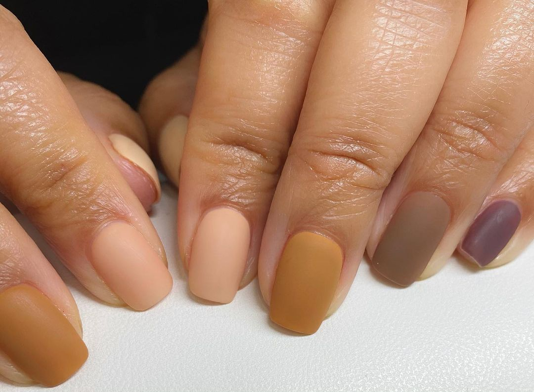 Person with matte nude nails
