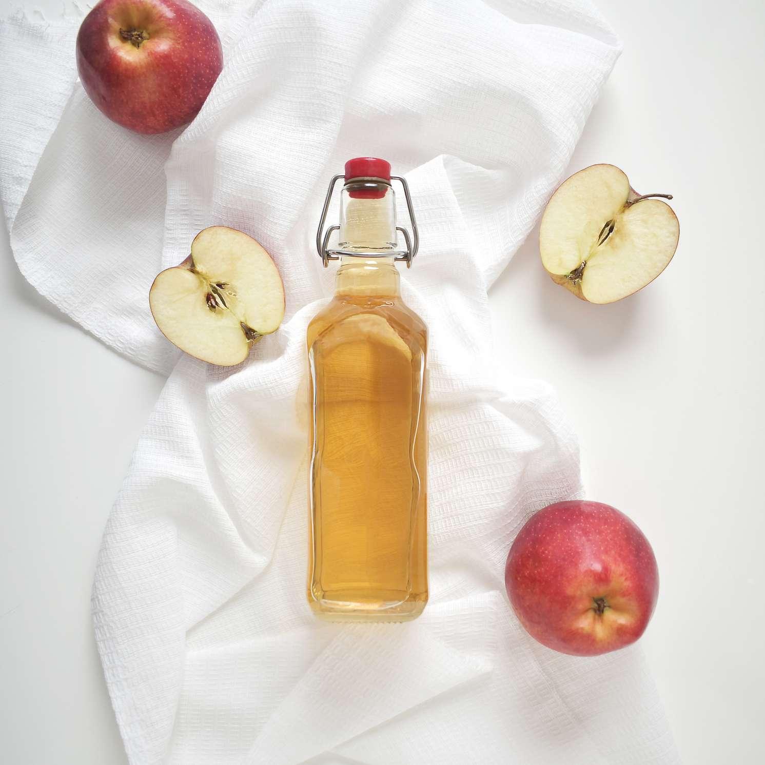 Apple cider vinegar or fermented fruit drink and organic apples on white