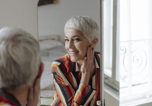 woman with gray hair looking at self in mirror