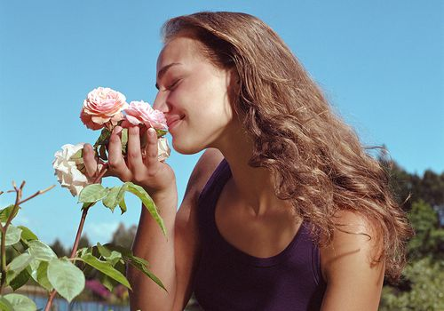 woman smelling rose outside