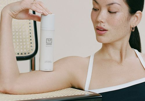 Woman balancing serum on arm