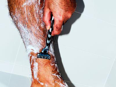 Man shaving his leg in the shower.