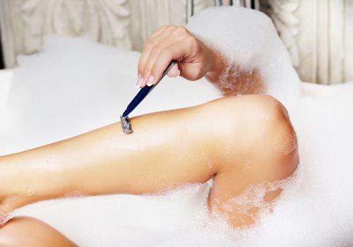 woman shaving legs in bubble bath