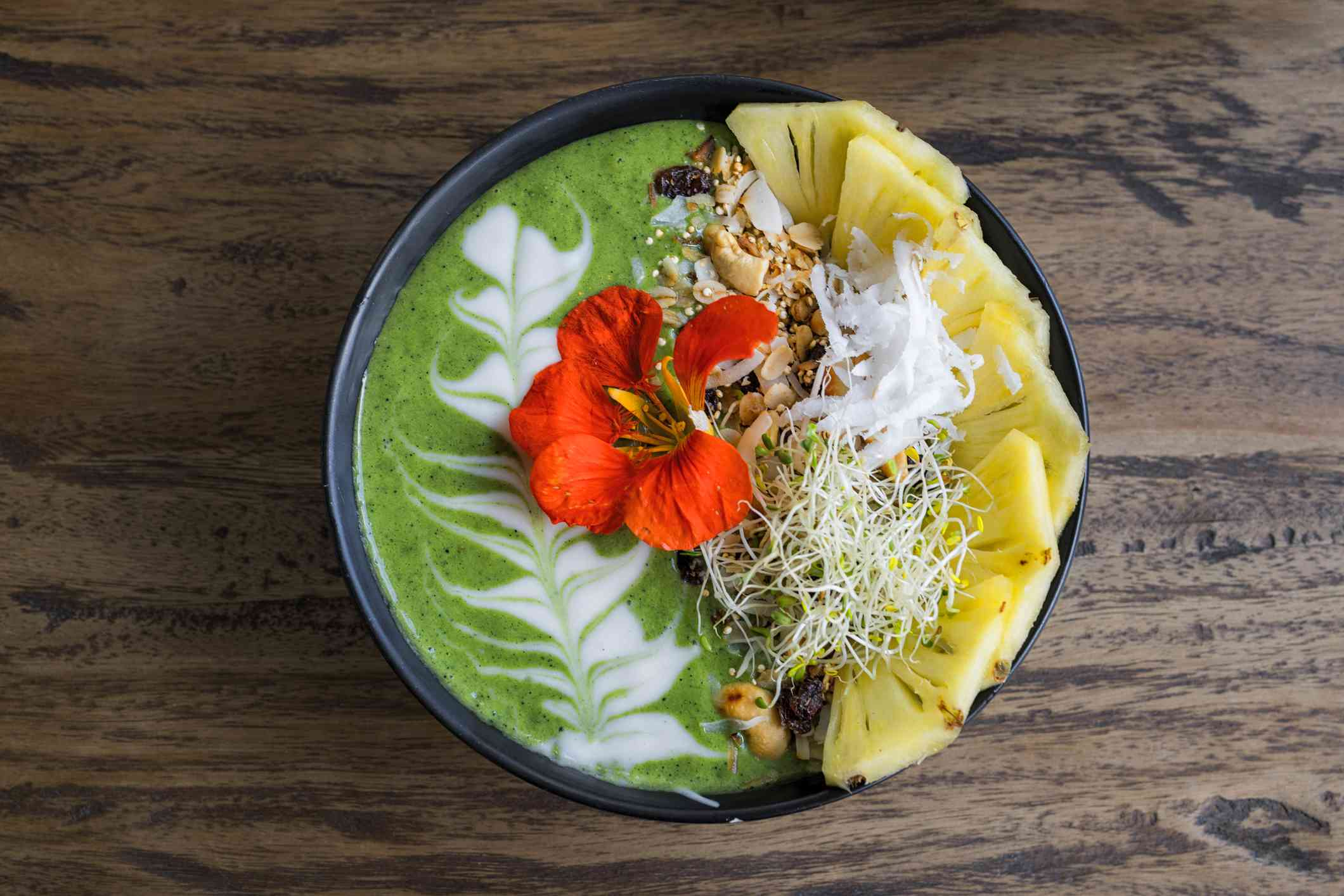 Decorated green smoothie bowl with pineapple and edible flower