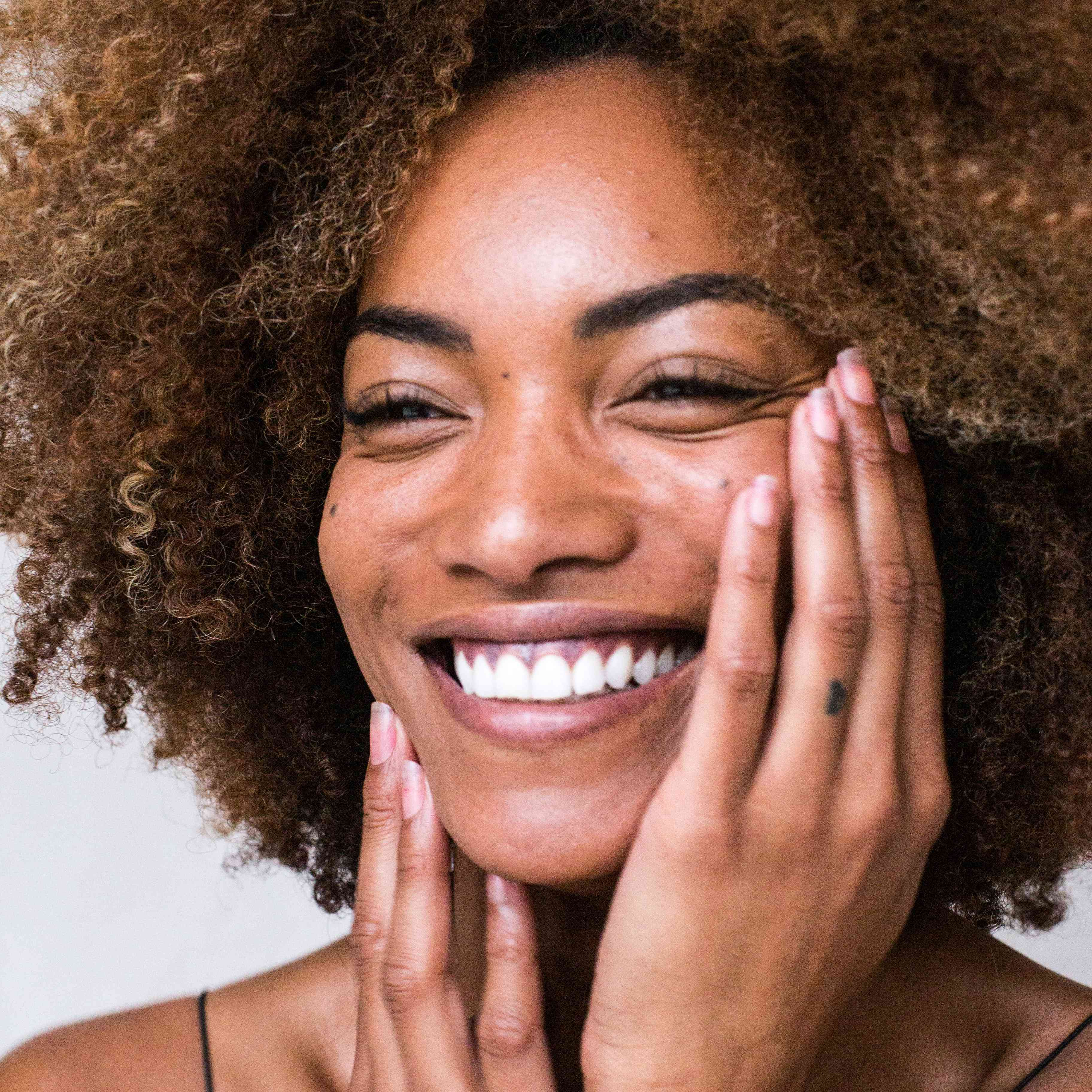 woman with glowy skin and curly hair smiling and touching her face