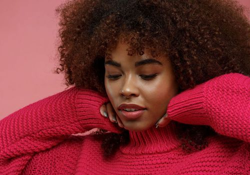 woman in red sweater with clear skin