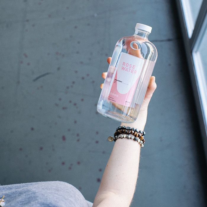 Hand with bracelets holding a glass bottle of rose water