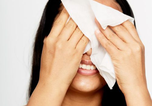 Woman holding a tissue that covers her eyes