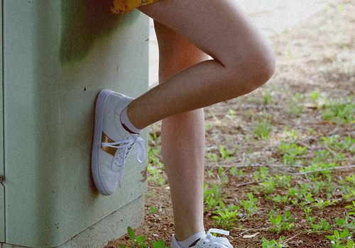 crop of person wearing yellow dress sneakers