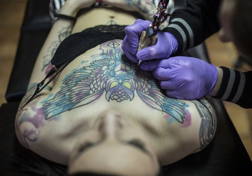 Young woman is getting a chest tattoo. About 25 years old, Caucasian brunette.