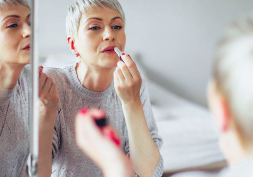 Woman with short gray hair putting on pink lipstick in the mirror