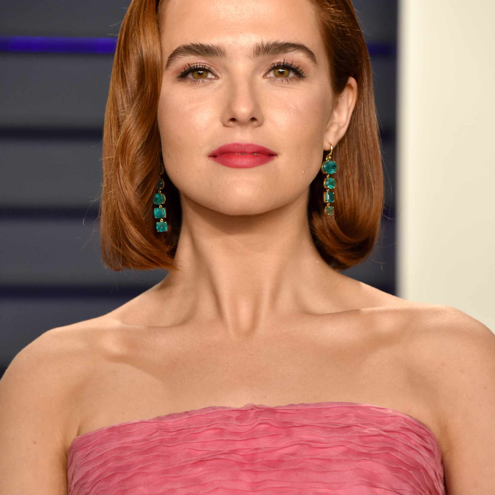 Zoey Dutch posing on the red carpet in a pink gown at the 2019 Vanity Fair oscar party