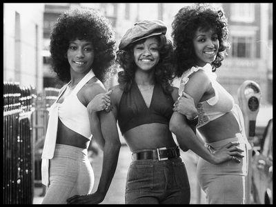 Three women wearing crop tops in the 1970s