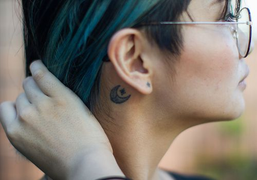 Asian woman with glasses and a crescent moon tattoo behind her eat