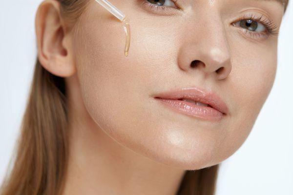 woman putting serum on skin