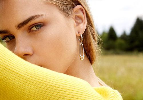 model in yellow shirt with hands over her head