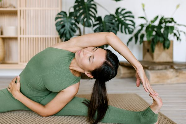 woman stretching in green workout set