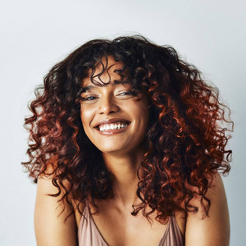 young brown femme with curly hair