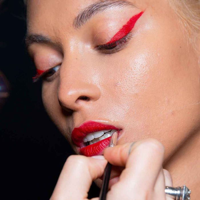 Model wearing neon red eyeliner and a bold red lip