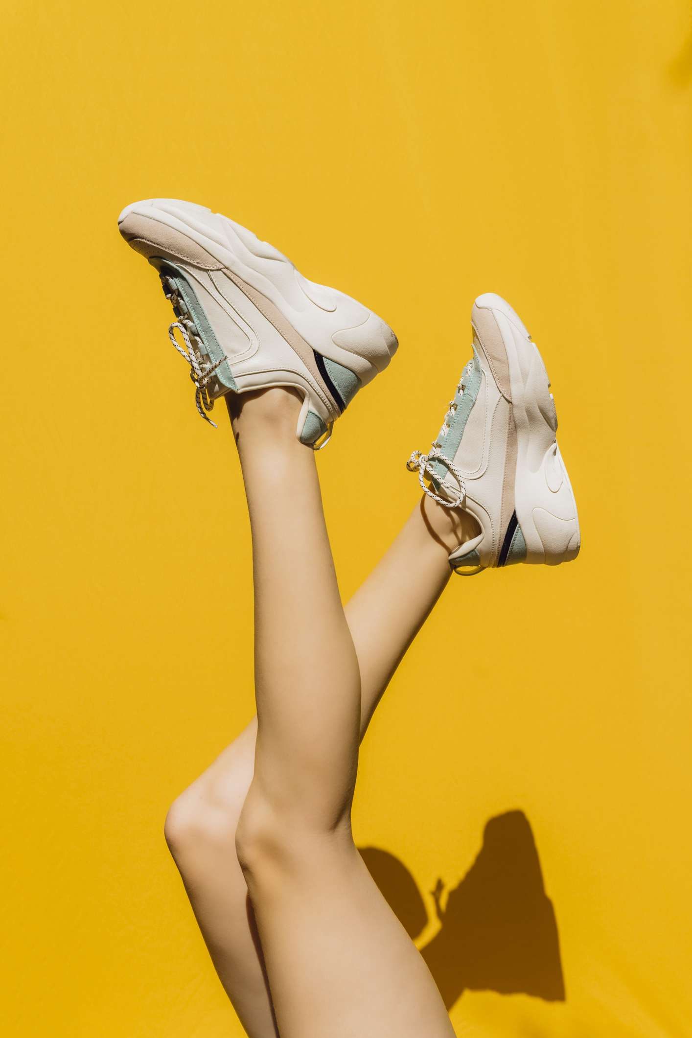 woman wearing sneakers against yellow background