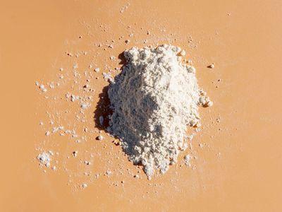 zinc pyrithione in powder form on an orange backgroun