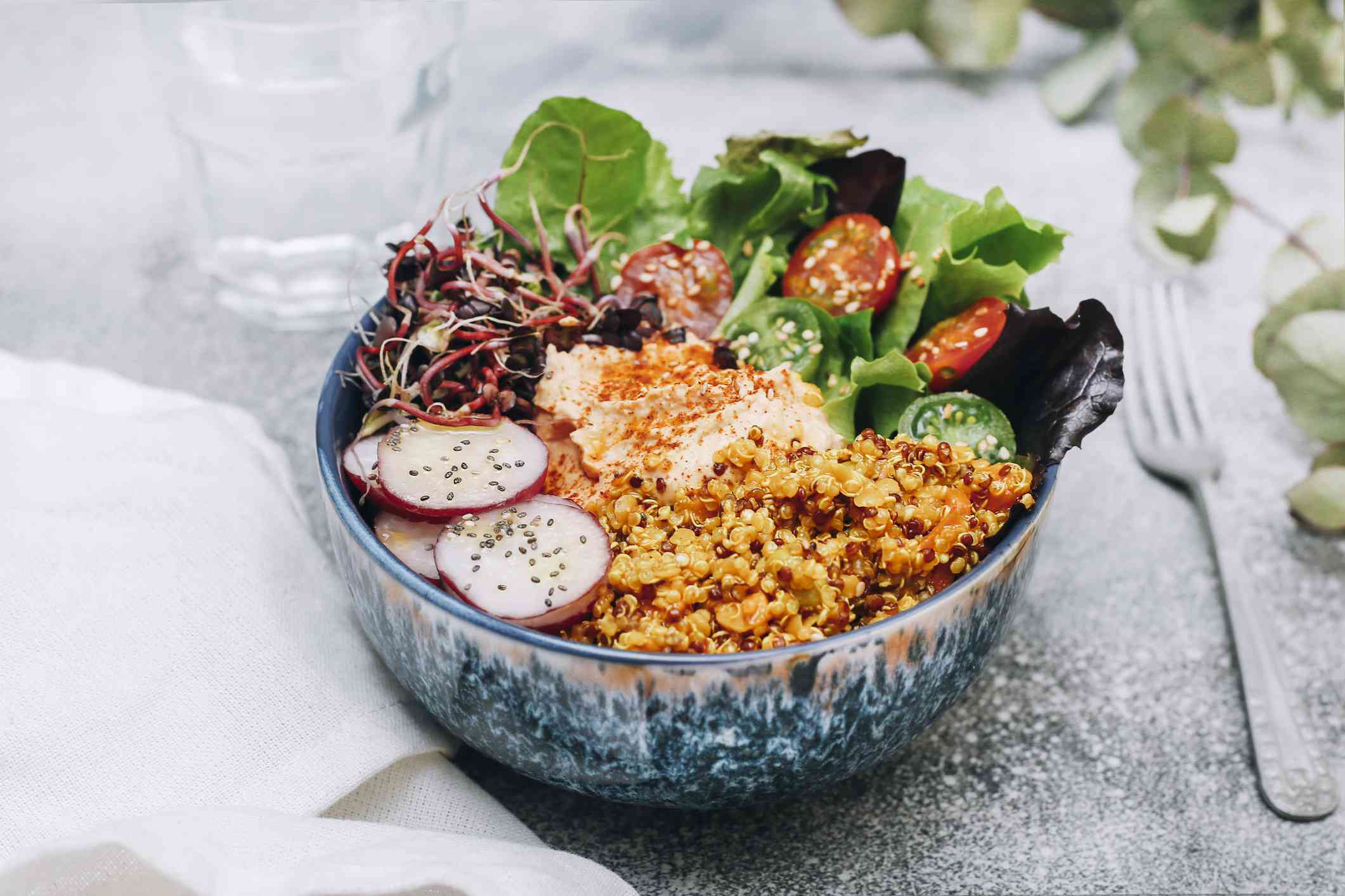 Bowl with quinoa, lettuce, radish, tomatoes and hummus. Sitting on table beside a fork.