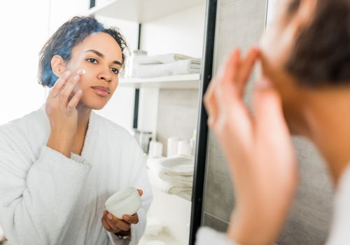 Woman applying cream to her face in bathroom mirror