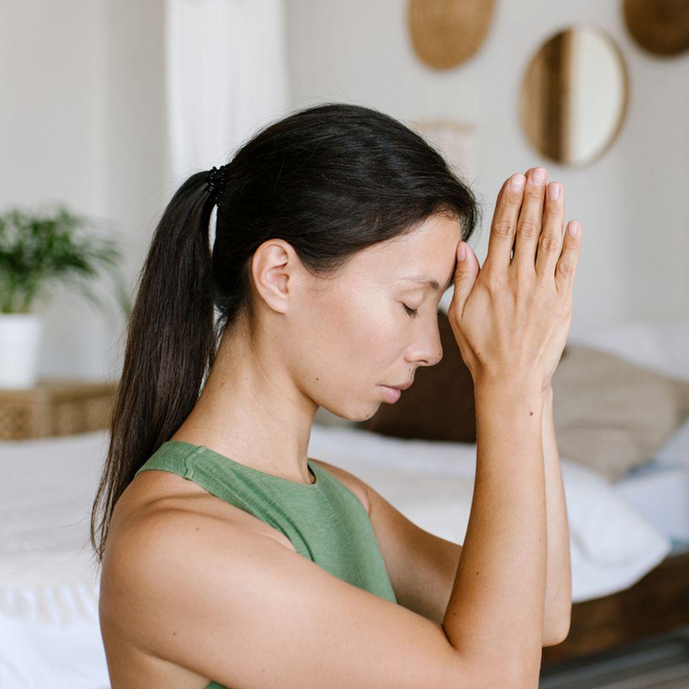 person meditating in bedroom