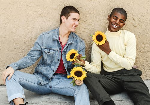 Two people sitting holding sunflowers