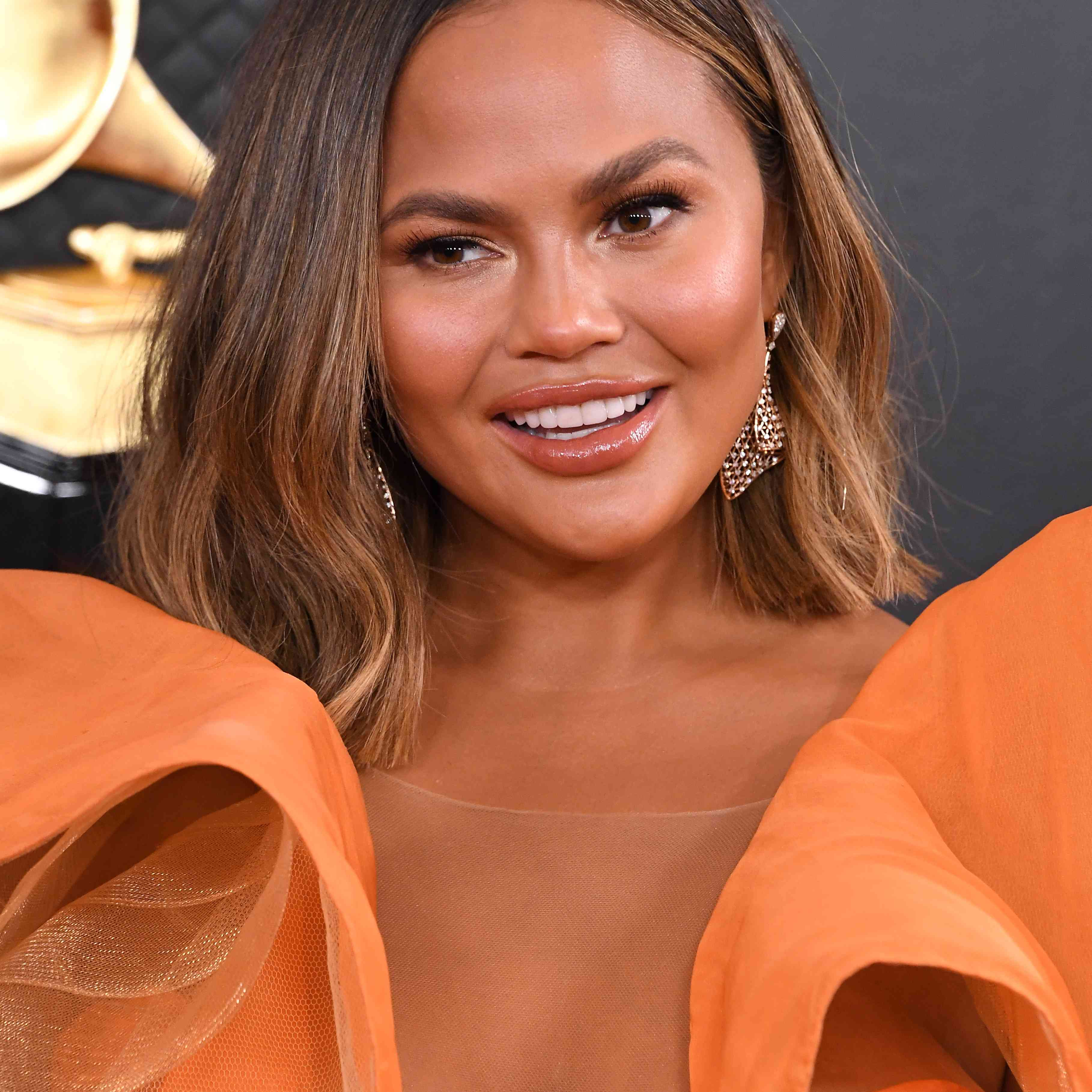 Chrissy Teigen with orange top and dangly earrings