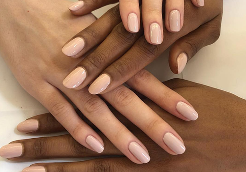 Caucasian and African American hands layered over one another, all featuring nude fingernails.