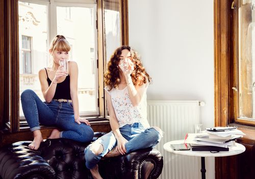 Two young women drinking water on a couch