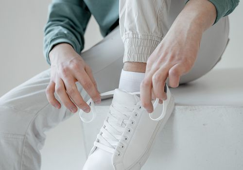 Guy sitting and tying a white sneaker
