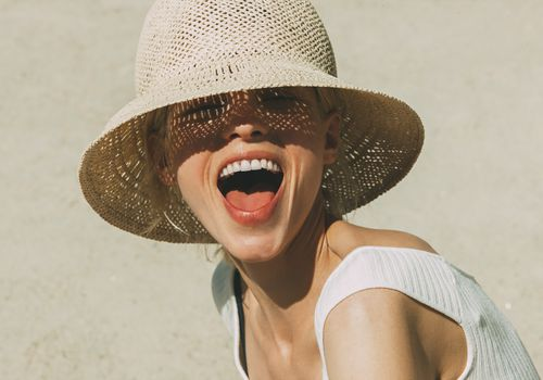https://www.gettyimages.com/detail/photo/portrait-of-laughing-blond-woman-wearing-summer-hat-royalty-free-image/763162939