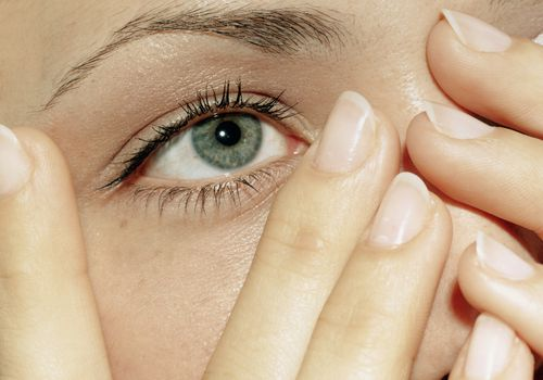 Woman with bare, clean nails touching face