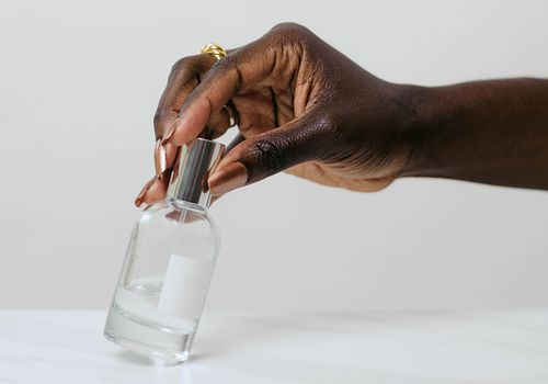 Manicured hand holding a perfumer bottle