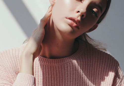 blonde girl in a pink sweater with natural light streaming in over a white background