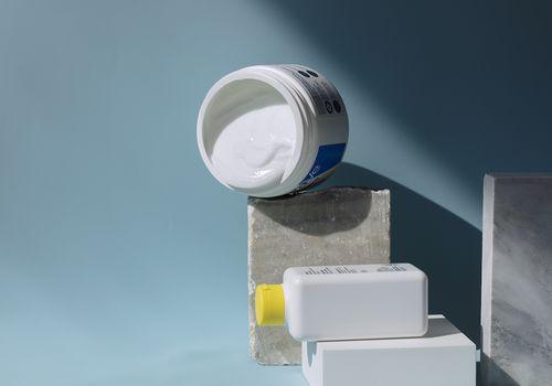 skin barrier creams on blue background
