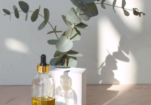 hair oil in bottle with dropper and eucalyptus plants