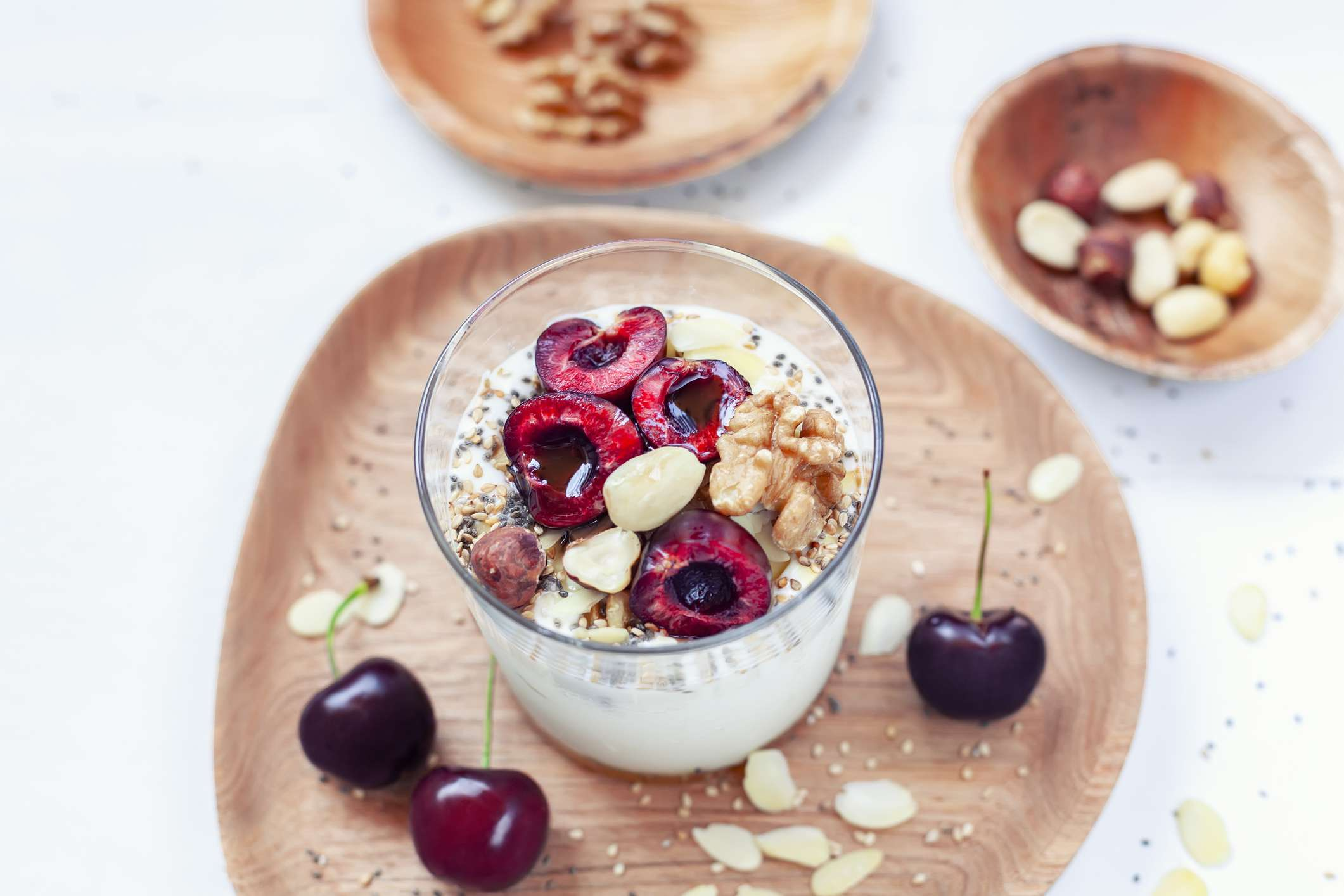 Glass of greek yogurt topped with cherries and nuts. Sitting atop a wooden plate with cherries and nuts on the side.