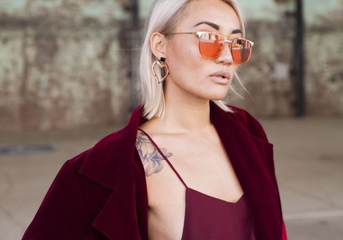 Blonde woman with sunglasses, and a shoulder tattoo peeking out from under a burgundy blazer