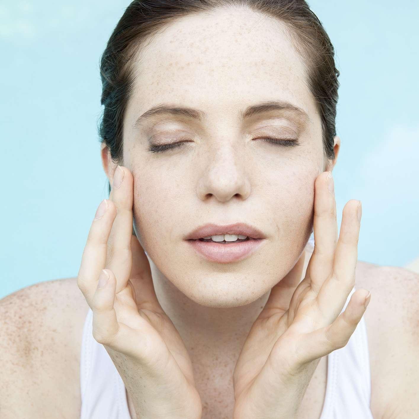 woman massaging/touching face