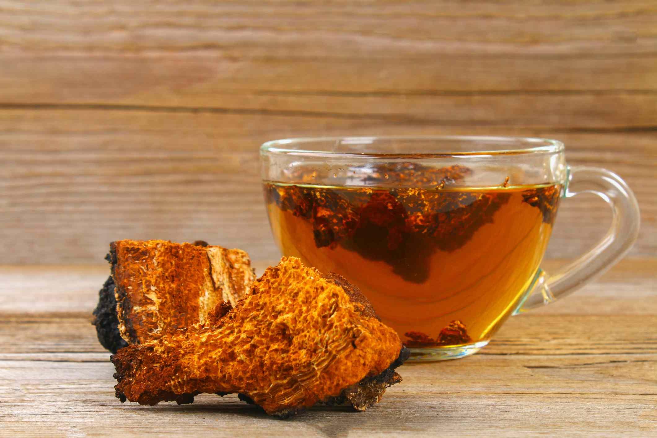 A cup of mushroom tea with a mushroom beside it.