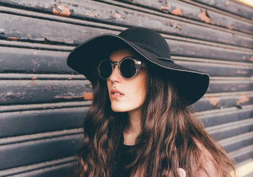 White woman with long, wavy brown hair, wearing sunglasses and black wide-brimmed hat