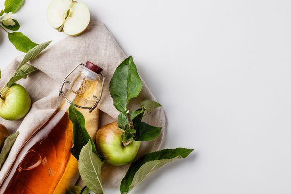 Close-Up Of Apple Cider Vinegar In Bottle Against White Background - stock photo
