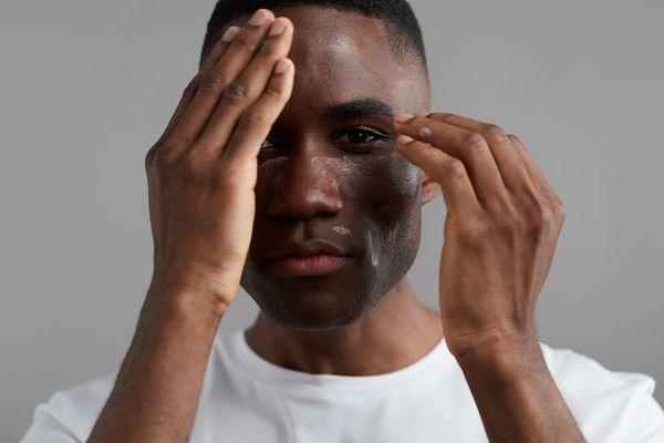 man moisturizing face